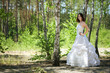 bride with dark-brown hair posing in forest