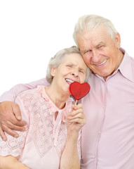 smiling old couple with red heart-shaped candy