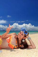 浜辺で横になる若い女性
