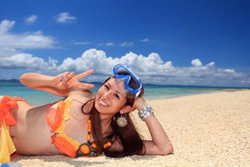 水納島の砂浜で寛ぐ若い女性