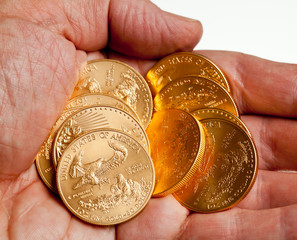 Hand holding stack of gold coins