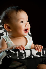 Chinese Asian toddler sitting in baby high chair