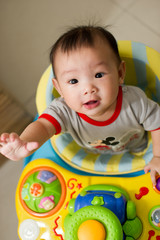 Chinese Asian toddler sitting in walker chair