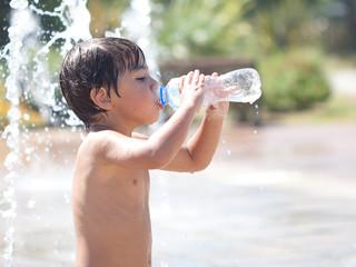 bambino bagnato che beve acqua dalla bottiglietta