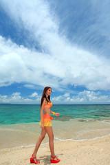 コマカ島の浜辺を散歩する水着の女性