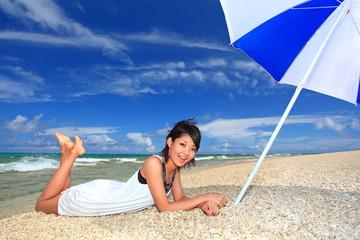 砂浜でリラックスする若い女性