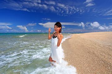 打ち寄せる波と笑顔の女性