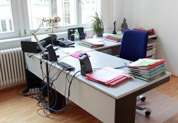 Schreibtisch im Büro mit Akten und moderner Bürotechnik
