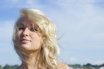 Closup portrait ot pretty smiling blonde against blue sky