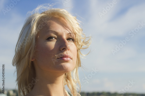 Closup portrait ot young pretty blonde against blue sky