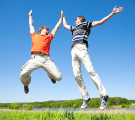 two young adult men jump into the air and clap their hands