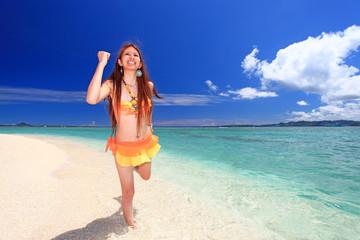 輝く砂浜を走る水着の女性