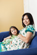 Pregnant Asian mother and her daughter