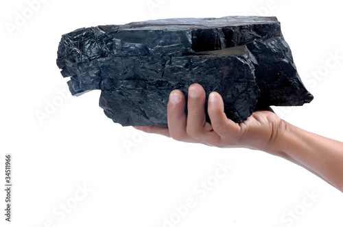 male hand holding a big lump of coal