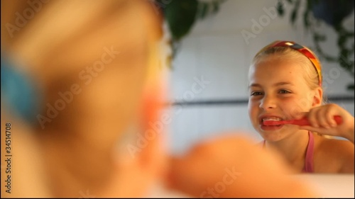 little girl brushing her teeth in front of a mirror