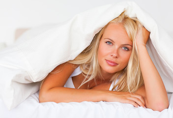 Blonde woman under a duvet