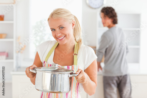 Woman posing with a boiler while her fiance is washing the dishe