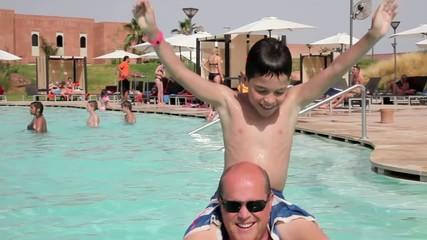 Père et fils jouant ensemble à la piscine