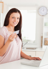 Woman showing credit card by notebook