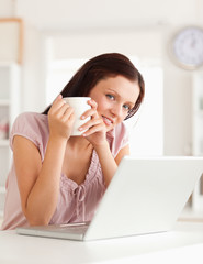 Woman holding cup of coffe at laptop