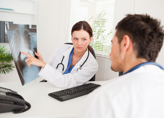 Female doctor showing other doctor x-ray
