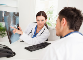 Female doctor showing x-ray to other doctor