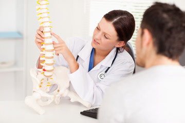 Female doctor pointing on bone in spine