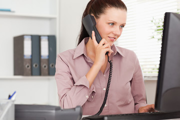 Businesswoman with telephone looking to screen