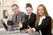 Positives Team im Büro zeigt die Daumen hoch.