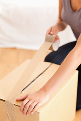 Close up of a woman preparing a cardboard
