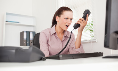 Depressed businesswoman shouting at telephone