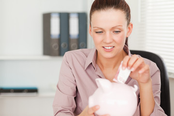 A female putting money into piggy bank