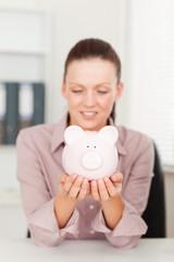 Businesswoman looking at piggy bank