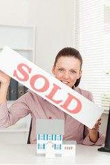 Businesswoman holding sold sign