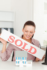Businesswoman holding sold sing above model house