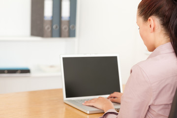 Businesswoman typing on her notebook