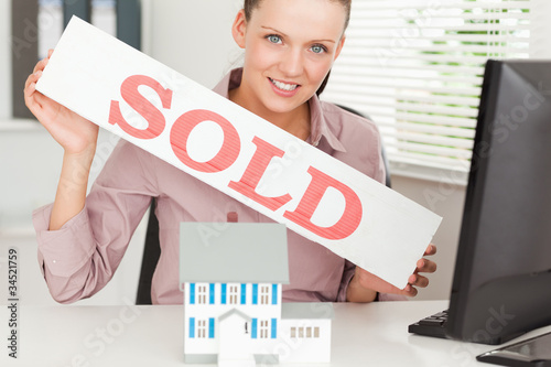 Businesswoman showing sold sign
