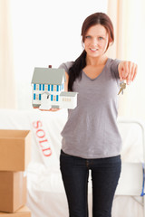 Portrait of a woman holding model house and keys