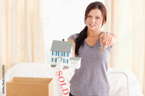 Young woman holding model house and keys