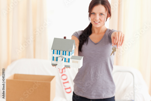 Beautiful woman holding model house and keys
