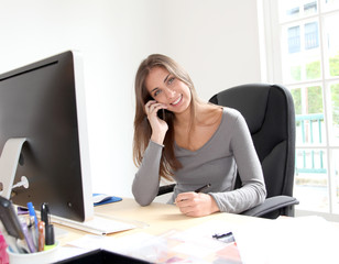Portrait of beautiful office worker sitting at her desk