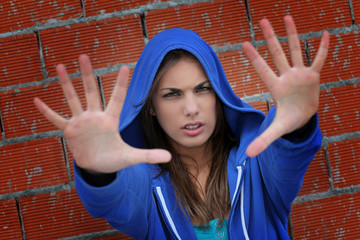 Teenager with blue sweater showing hand to camera