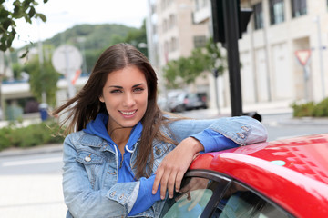 Young woman standing by red car