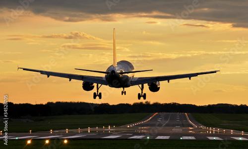 Foto op Plexiglas Vliegtuig Lądowanie o zachodzie