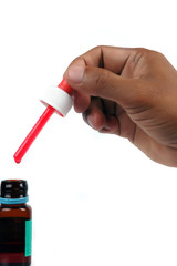 male hand holding a syrup medicine dropper