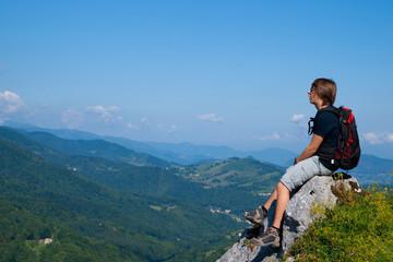 Jeune homme assis sur un rocher