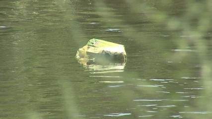 Garbage swim in the river with pan