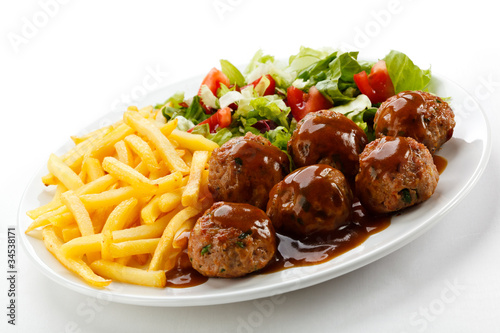 Roasted meatballs, French fries and vegetable salad