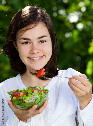 Girl eating vegetable salad