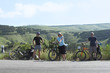 three bicycle tourists standing on road in mountains in Crimea,